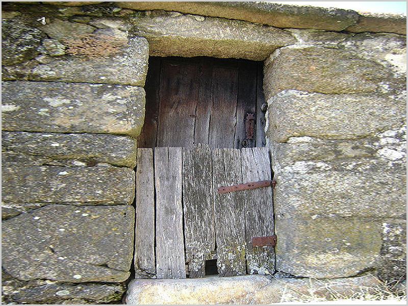 Porta de madeira com postigo em casa de pedra antiga - capeiaarraiana.pt