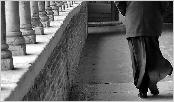 Padre caminhando num claustro