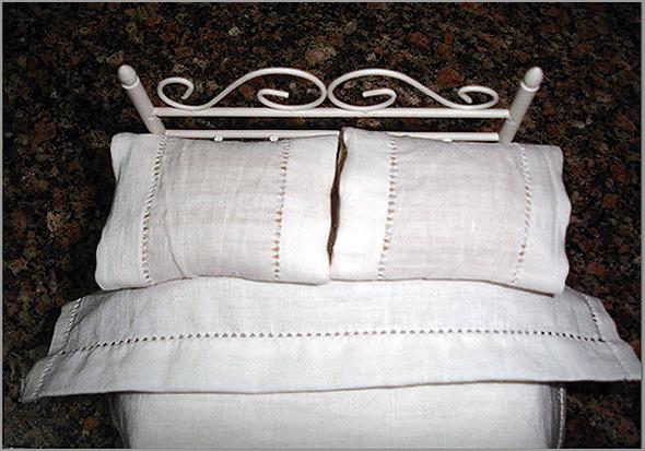 Cama com lençóis e almofadas de linho
