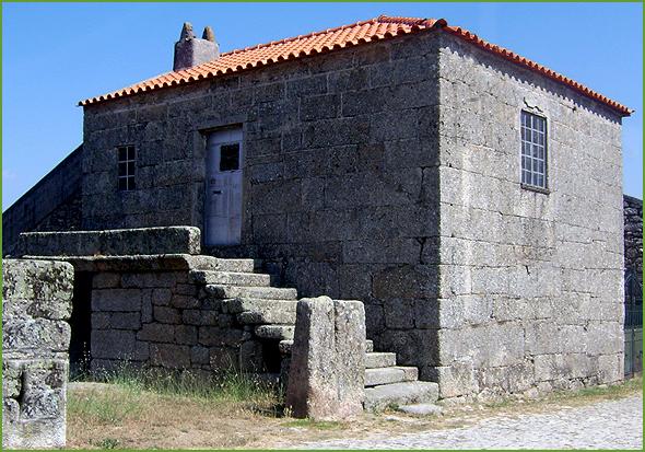 Casa tradicional de altos e baixos, o espaço por baixo das pedras do balcão servia de galinheiro e a entrada para a loja fazia-se por baixo do mesmo